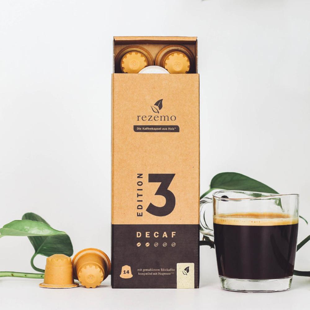 rezemo 14er-Verpackung Decaf Edition 3 mit Kaffeetasse daneben