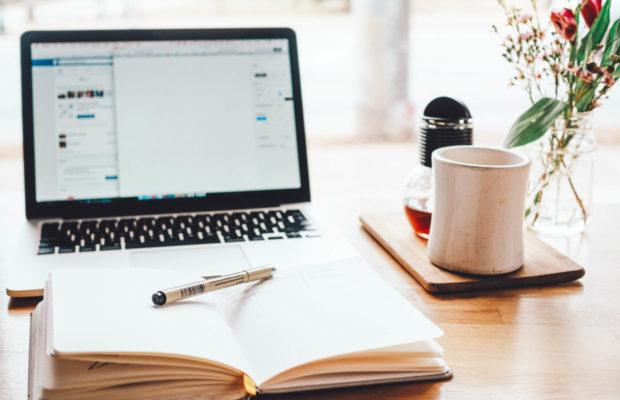 Notizbuch, Laptop und Kaffeetasse auf Schreibtisch in typischer Homeoffice-Situation