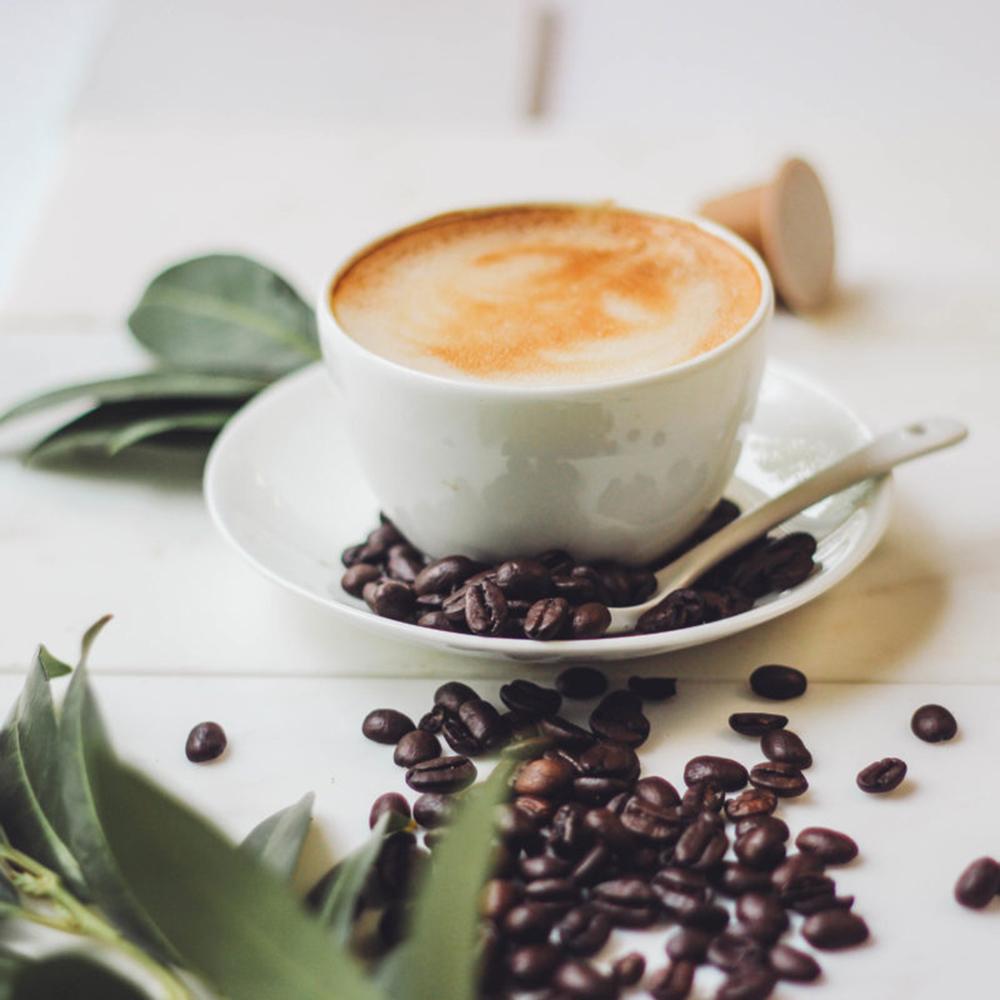 Milchkaffee, Kaffeebohnen und gruene Blätter auf Marmorplatte