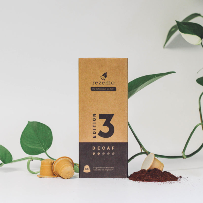 14er-Verpackung rezemo Decaf Edition 3 neben Kaffeepulver und rezemo Kaffeekapseln