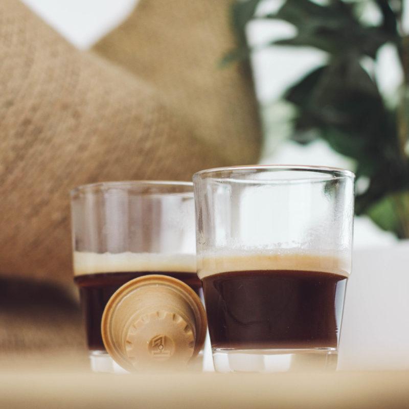 Zwei Tassen frisch gebruehter rezemo Espresso Editionb 1 neben Holzkapsel mit Kaffeesack im Hintergrund