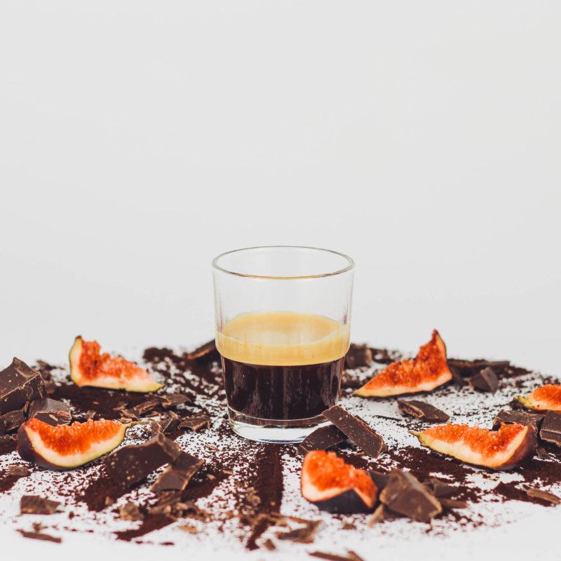 Frisch gebruehter Espresso Edition 4 neben Schokoladensplittern und Feigen-Scheiben