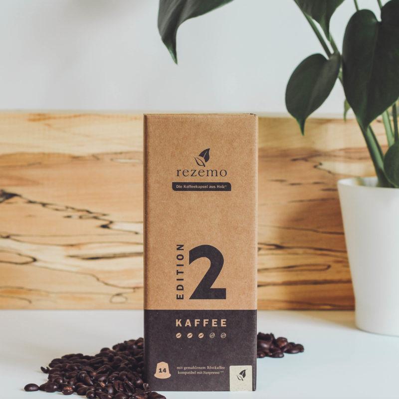 14er-Verpackung rezemo Kaffee Edition 2 mit Kaffeebohnen und Holz im Hintergrund