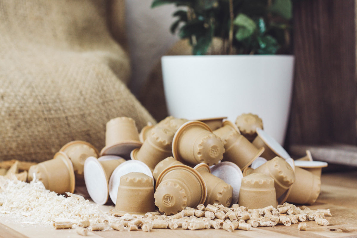 rezemo Kaffeekapseln liegen neben den Rohstoffen Holzspänen und PLA