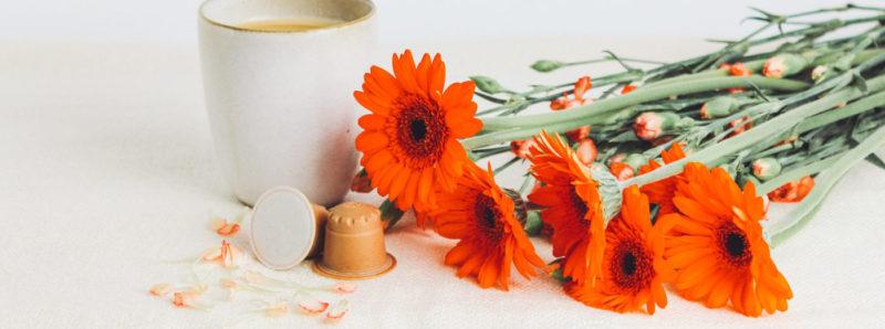 rezemo Kaffee neben Blumenstrauss