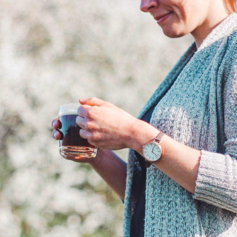 Frau mit Kaffeetasse in den Händen vor weißem Busch im Freien