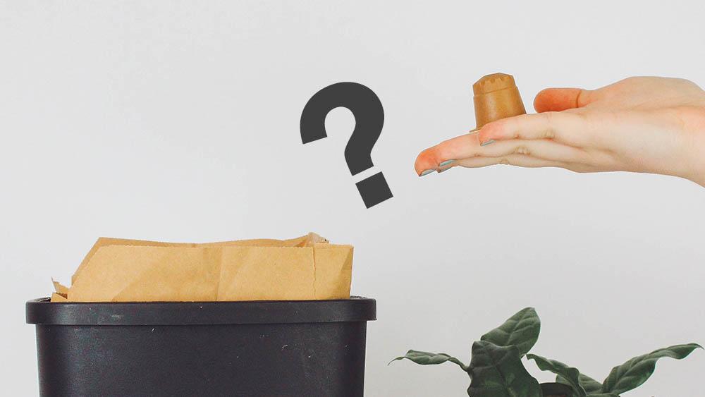 rezemo Kaffeekapsel auf Hand vor einem Bio-Mülleimer