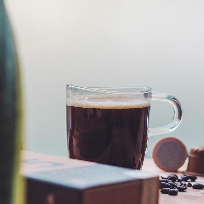 rezemo Kaffee Edition 5 in Tasse neben Kaffeebohnen und Kapseln