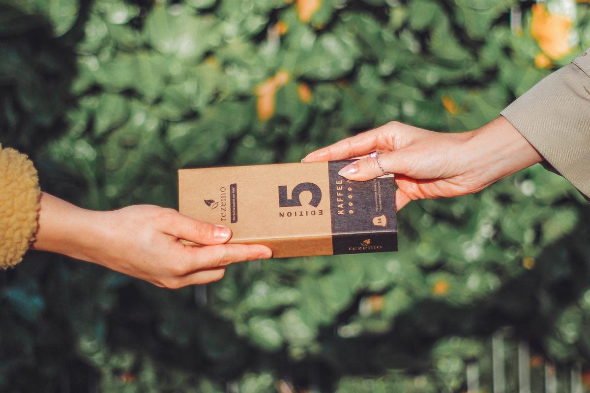 Eine Packung nachhaltige rezemo Kaffeekapseln wird von einer Hand in einen Andere übergeben, eine grüne Hecke befindet sich im Hintergrund