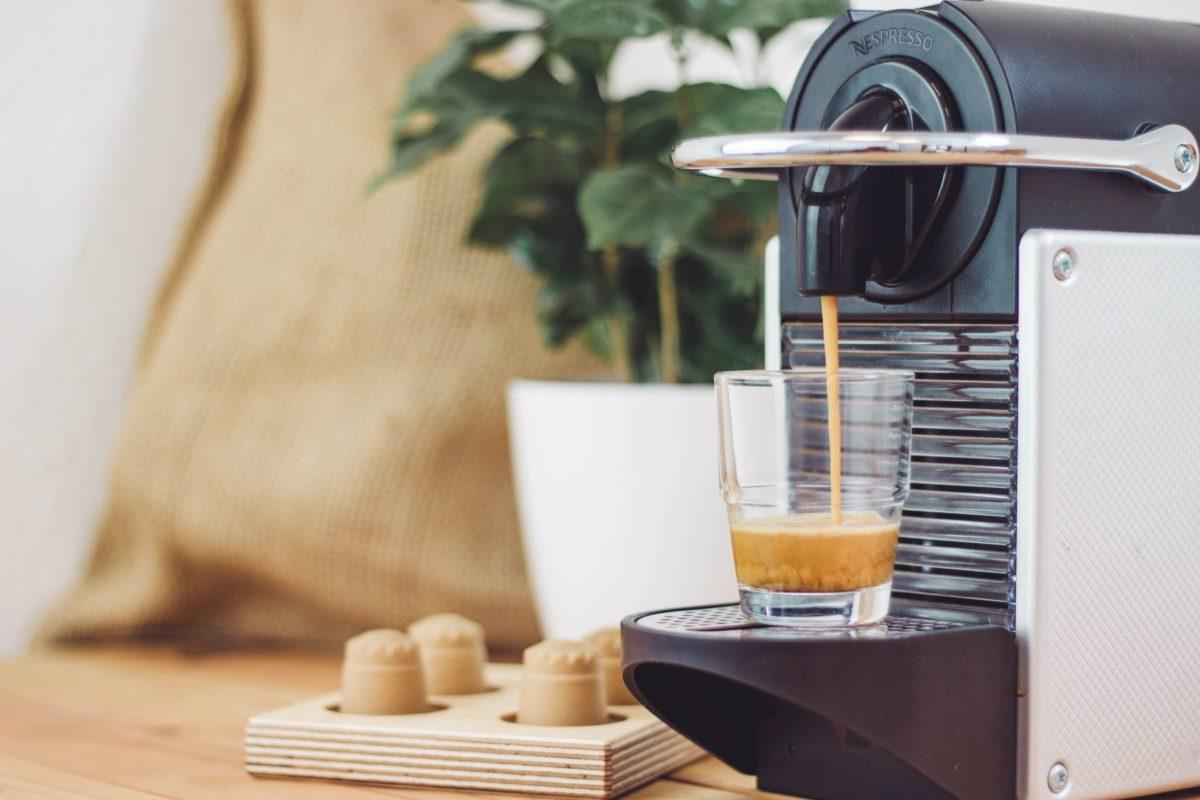 rezemo Espresso wird aus Kapselmaschine aufgebrüht, im Hintergrund eine Kaffeepflanze