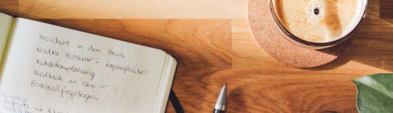 Schreibtisch mit Notizbuch, Kugelschreiber und umweltfreundlichem rezemo Kaffee
