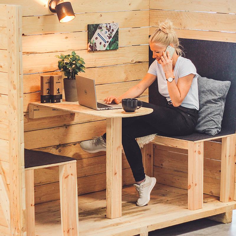 Mitarbeiterin Janina arbeitet in der selbstgebauten Holzbox