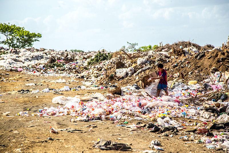 Junge sammelt Plastik am Strand